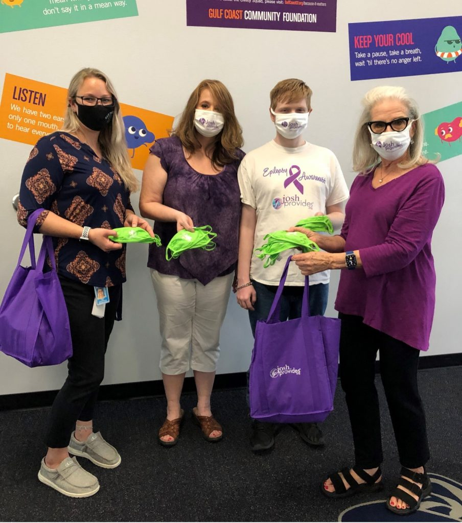Nicole Meo, Assistant Principal at Oak Park School accepts donation of masks from Laura Dansky, parent, Collin Robinson, student, and Sandi Chapnick, co-founder of JoshProvides in honor of Purple Day.